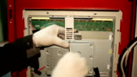 The scientist twists the screws using screwdriver in the switchboard video