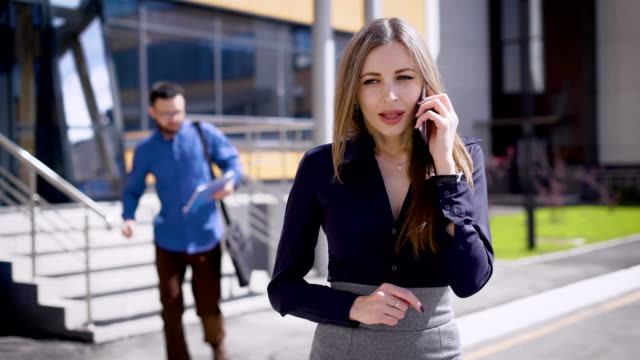 The scraper of the company runs up to the chief, so that she signs in the records for the year the papers, the woman is talking on the mobile phone video