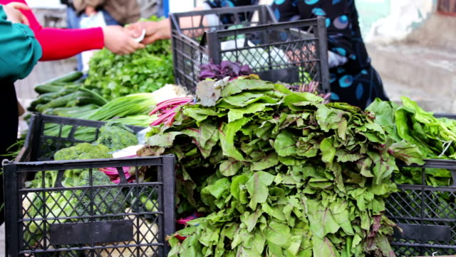 The seller in the market sells greens to buyer. A woman buys fresh vegetables on the market video