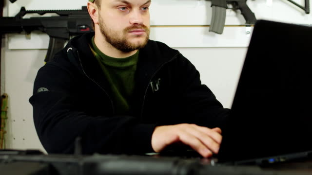 The seller of weapons inspects the goods in the store with a laptop. Against the background of the showcase with samples of airsoft weapons video
