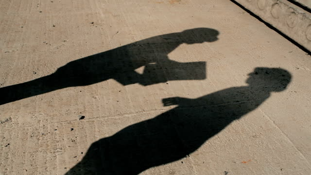 The shadows of two men on the concrete video