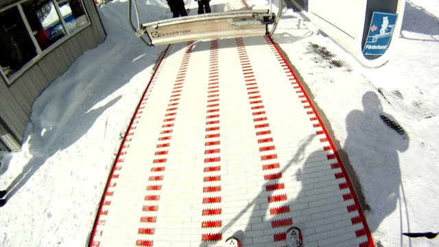 The skier sits on the ski lift. First-person view video