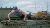 The soldier pushed on the tank. Training on a military base video