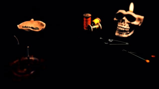 the sorcerer prepared a voodoo doll for ritual and put on the altar with a skull ,a candle,needles and thread video
