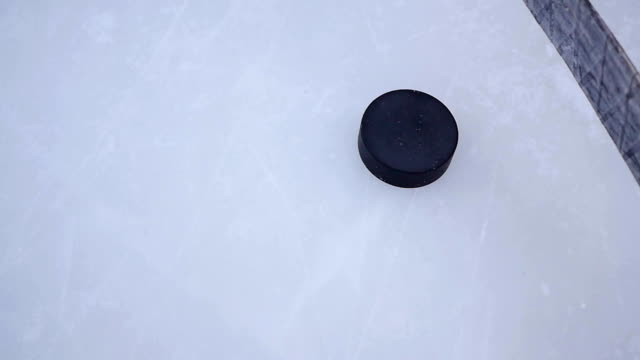 the stick controls dribbling the puck on the ice rink closeup video
