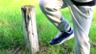 The strong man strike off tree stump with one hit of leg. Slowly video