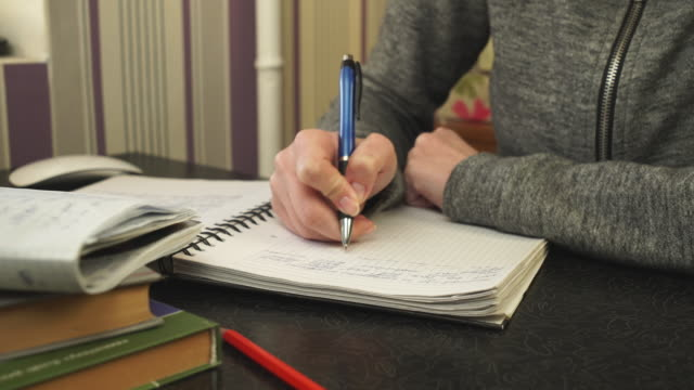 The student writes in a notebook video