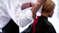 The stylist removes the cape from the client. Beauty saloon video
