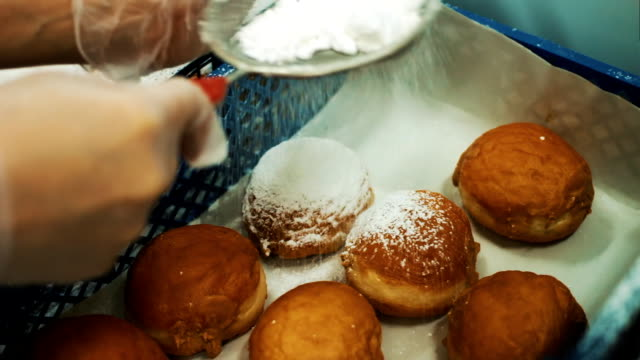 The sugar powder is poured onto the donut. Confectionery production of donuts. Sugar on a donut video