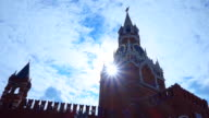 The sun shines through the Spasskaya Tower of the Kremlin against the blue sky video
