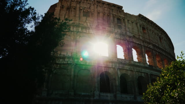 The sun's rays shine through the arches of the famous Colosseum in Rome. Steadicam shot video