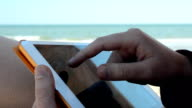 The tablet in the girl's hands on the beach. video