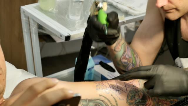 The tattooer is making the tattoo on hand in tattoo salon video
