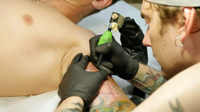 The tattooer makes the tattoo on guy's arm video
