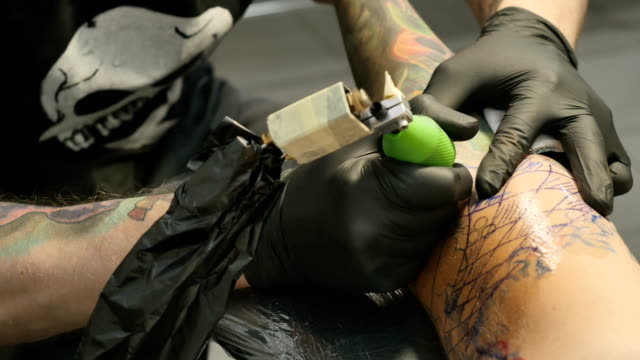 The tattooist is making the tattoo on the man's hand video