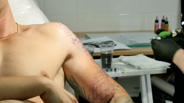 The tattooist makes the tattoo on man's arm in tattoo salon video