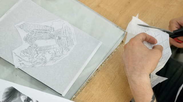 The tattoooist cuts with scissors a tracing paper with sketch video