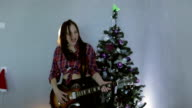 The teenage girl playing guitar, singing song and dancing near christmas tree. video