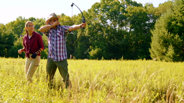 The teenager daughter teaches his father to shoot a bow video