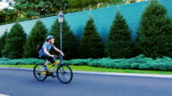 The teenager thirteen rides a bicycle along a green fence video