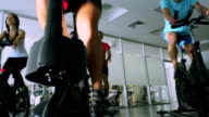 The trainer and young sportsmen are training on the exercise bikes in the gym video