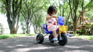 The two-year old cute asian girl riding a toy car alone on street video