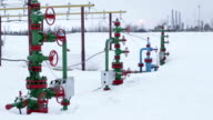 The valves at the wellhead production. In the background processing plant gas and oil video