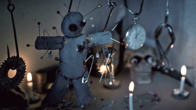 the voodoo doll swinging on the hook over the ritual table video