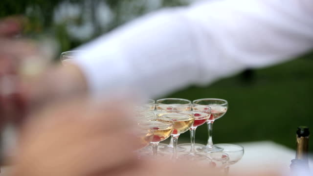 The waiter distributes to guests champagne video