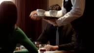 the waiter has brought coffee to a couple video