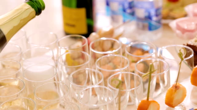 The waiter pours champagne into glasses, buffet table with plates and utensils. Catering, on-site restaurant video