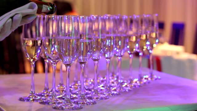 The waiter pours champagne into glasses, champagne glasses on the buffet table, the hall of the restaurant or hotel, the waiter's hand in a white glove with a bottle of champagne, indoor, close-up video