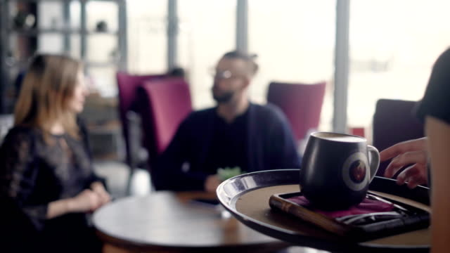 The waiter wears a large cappuccino cup for the young couple on the tray, who performs an aperitif in a restaurant, a man and a woman talk about the past weekend video