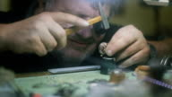 The watchmaker is repairing and maintaining watch - hammering , hard work video