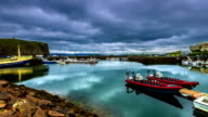 The water in the port reflects floating clouds. Stykkishólmur Harbour, Iceland video