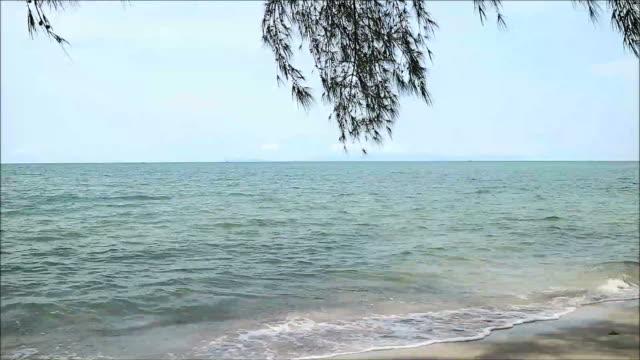 The wave crashing sandy beach under pastel blue sky, Gulf of Thailand video
