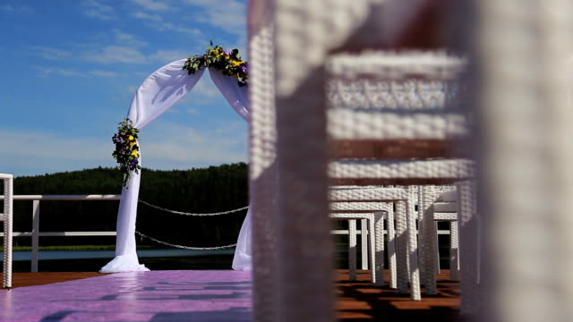 The wedding arch with flowers is seen through the cane chairs made of wood. It's located on the cost of the lake with beautiful landscape video