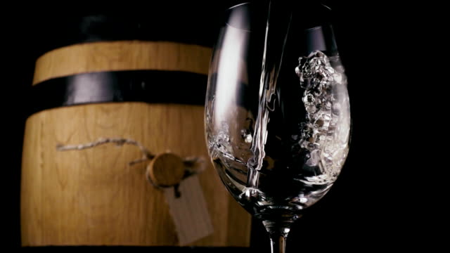 The wine is pouring into the glass in the background a wine barrel. Slow mo video