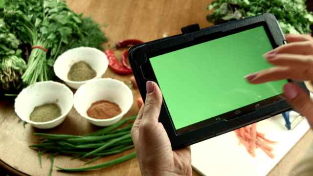 The woman cooks food using tablet video