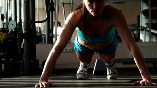 The woman in sportswear does push-ups in a gym video