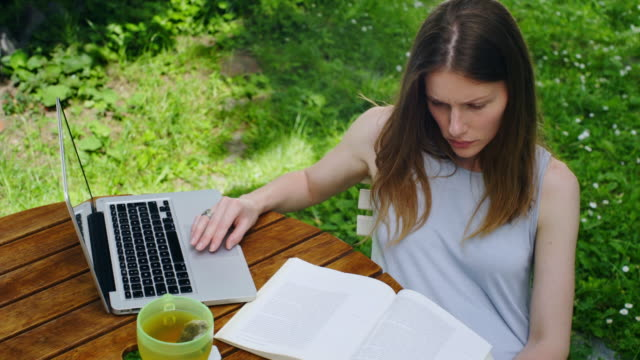 The woman in the garden reads the book and uses the laptop video