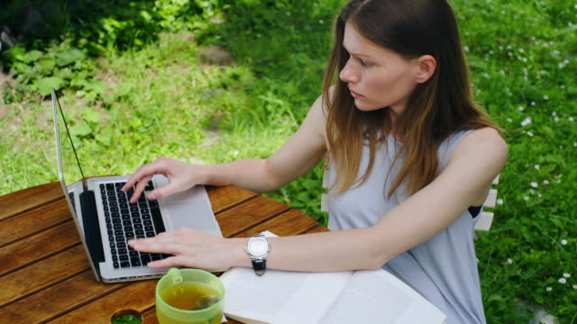 The woman in the garden reads the book and uses the laptop. video
