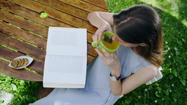 The woman in the garden reads the book. video
