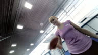 The woman playing the ping-pong at the court, the camera incline video