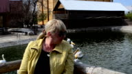 The woman poses against a pond video