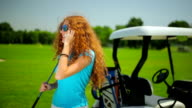 The woman talking on the phone near the cart video