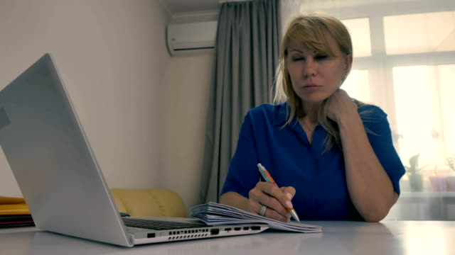 The woman-freelancer is writing on the paper at the table video