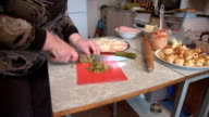 The woman's hands cut the marinated cucumber into slices, preparing pizza. video