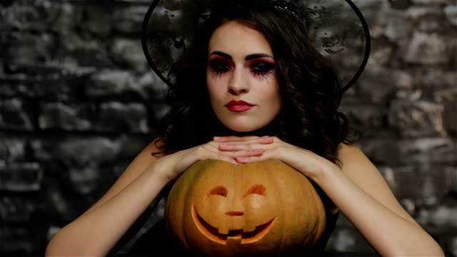 The woman-sorceress posing with pumpkin video