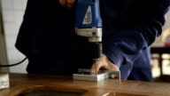 The worker drills holes to install the lock on the door. video